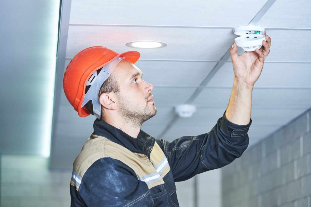 Electrician working on fire alarm system